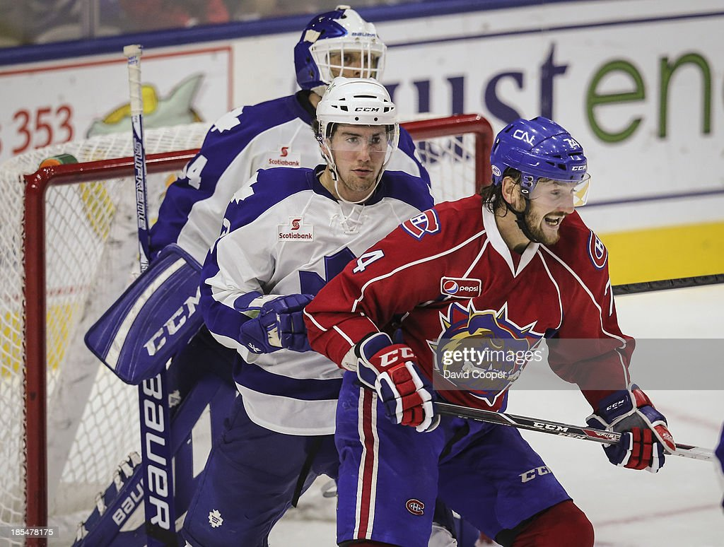 Marlies Andrew MacWilliam (2) tries to clear Hamilton Bulldogs Nick Tarnasky (74) from the front of the net during the game. The Toronto Marlies defeated the Hamilton Bulldogs 2-1 at the Ricoh Coliseum in Toronto, October 20, 2013.