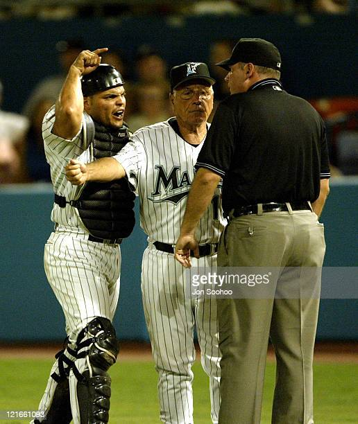 Marlins catcher Ivan Rodriguez is separated from umpire Scott Nelson by Manager Jack Mckeon after being tossed in controversial play