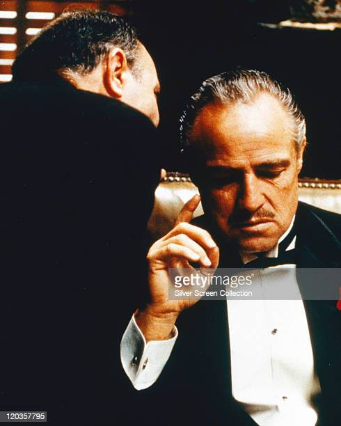 Marlon Brando US actor listens as a man speaks into his ear in a publicity still issued for the film 'The Godfather' 1972 The mafia drama directed by...