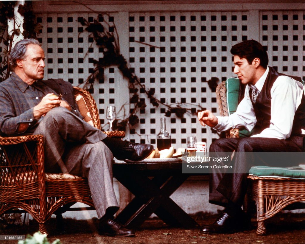 Marlon Brando US actor sitting opposite Al Pacino US actor both sitting on wicker garden chairs in a publicity still issued for the film 'The...