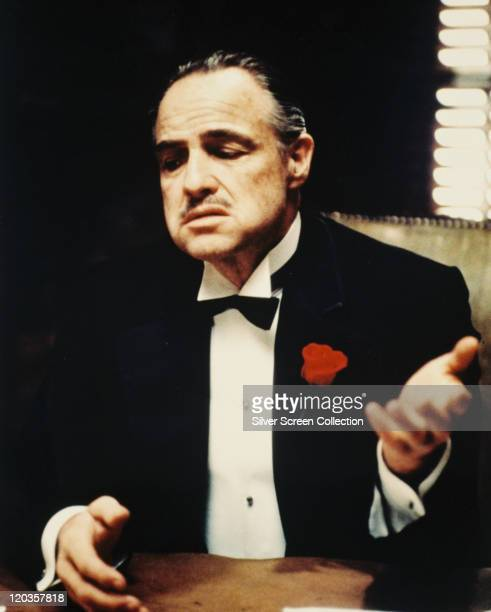 Marlon Brando US actor wearing a black dinner jacket with a white shirt and black bow tie with a red flower on his lapel in a publicity still issued...