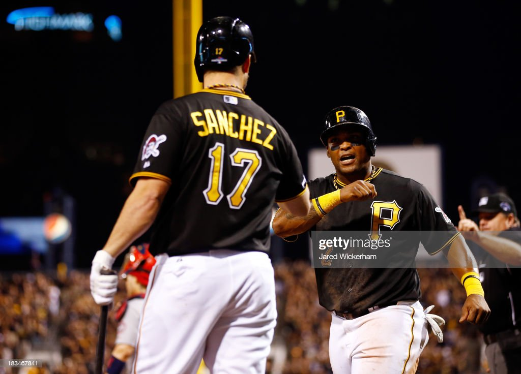 Marlon Byrd is congratulated by Gaby Sanchez of the Pittsburgh Pirates after scoring against the St Louis Cardinals during Game Three of the National...