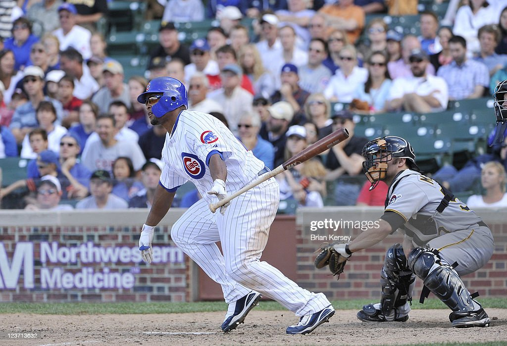 Marlon Byrd #24 of the Chicago Cubs follows through on an RBI single scoring teammate Carlos Pena #22 as catcher Michael McKenry #55 of the Pittsburgh Pirates watches during the eighth inning at Wrigley Field on September 4, 2011 in Chicago, Illinois.
