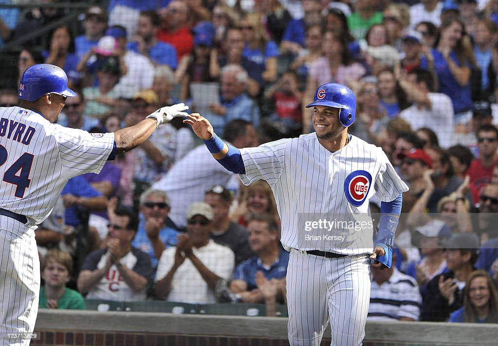 Marlon Byrd #24 (L) of the Chicago Cubs high-fives teammate Aramis Ramirez #16 after Ramirez scored on an RBI single hit by Bryan LeHair during the sixth inning against the Pittsburgh Pirates at Wrigley Field on September 4, 2011 in Chicago, Illinois. The Cubs won 6-3.