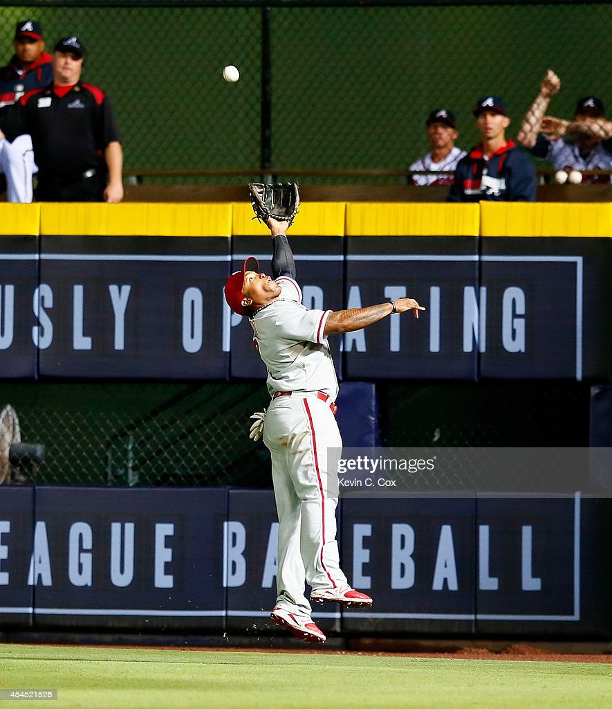 <a gi-track='captionPersonalityLinkClicked' href=/galleries/search?phrase=Marlon+Byrd&family=editorial&specificpeople=217377 ng-click='$event.stopPropagation()'>Marlon Byrd</a> #3 of the Philadelphia Phillies leaps to catch a deep ball hit by Tommy La Stella #7 of the Atlanta Braves in the seventh inning at Turner Field on September 2, 2014 in Atlanta, Georgia.