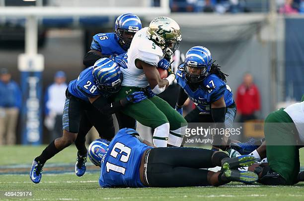 Marlon Mack of the South Florida Bulls is tackled by Andrew Gaines Tank Jakes and Fritz Etienne of the Memphis Tigers on November 22 2014 at Liberty...
