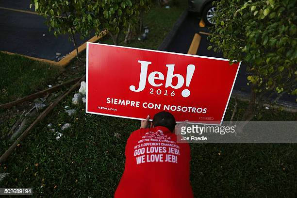 Marlon Motero puts up campaign signs for Republican presidential candidate and former Florida Governor Jeb Bush before he arrives for a meet and...