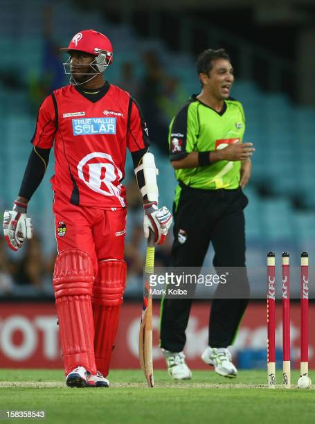 Marlon Samuels of the Renegades looks dejected after being bowled by Azhar Mahmood of the Thunder celebrates taking a wicket during the Big Bash...