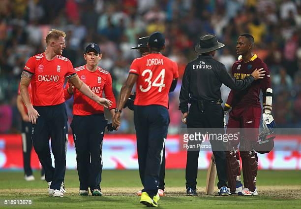 Marlon Samuels of the West Indies is spoken to by the umpires after he celebrates after Carlos Brathwaite of the West Indies hit the second six of...