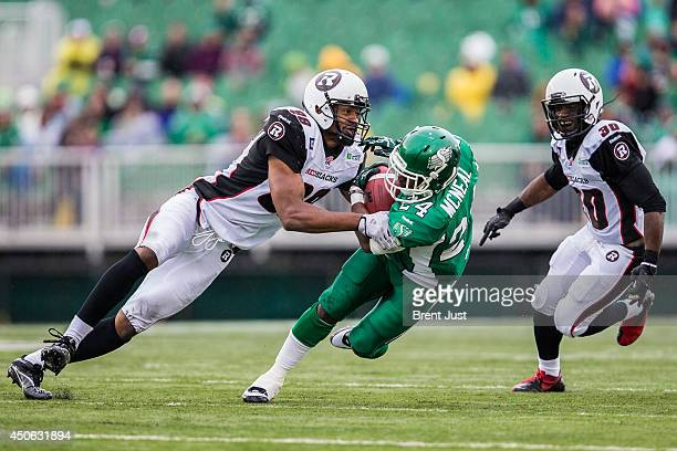 Marlon Smith of the Ottawa RedBlacks brings down Curtis McNeal of the Saskatchewan Roughriders during preseason week B of the 2014 CFL season in a...