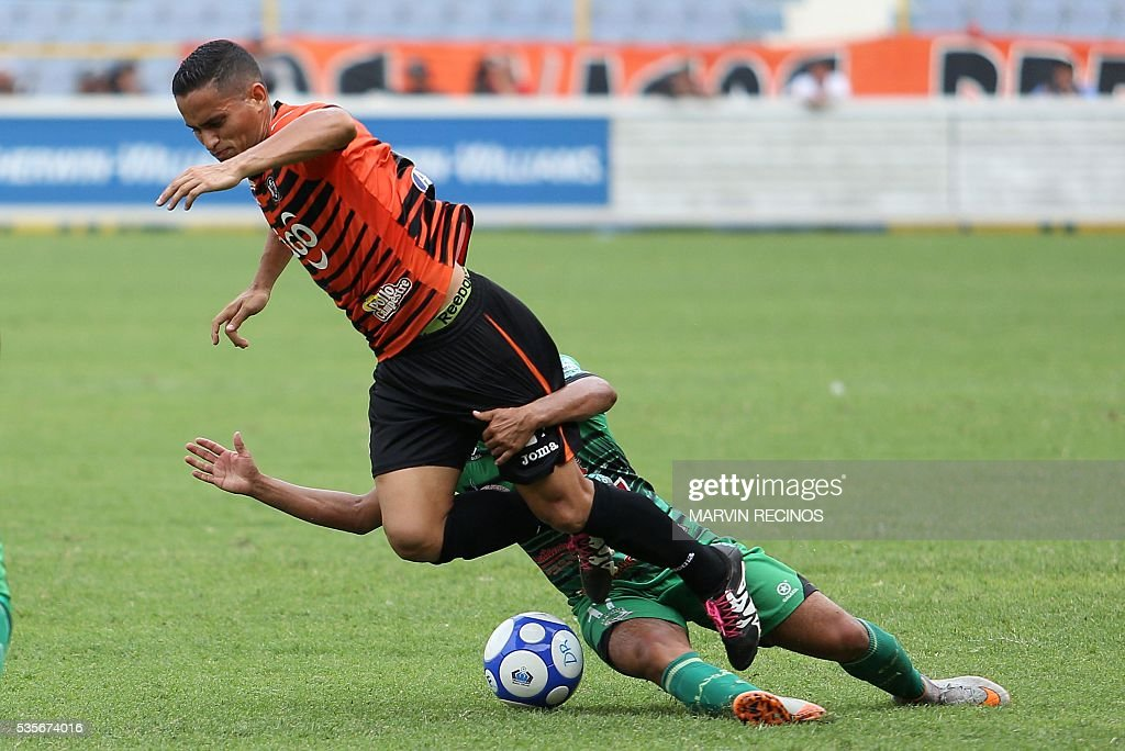 Marlon Trejo (L) of Aguila is tackled by Eduardo Lizama (R) of Dragon during their 2016 El Salvador's Clausura tournament final football match in San Salvador on May 29, 2016. / AFP / Marvin RECINOS