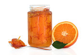 """""""Marmalade in a jar with half an orange, leaf and jam in a spoon over white background."""""""