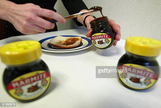 Marmite the traditional British vegetable paste is spread on a slice of bread during a lunch break in London 22 February 2002 The brand celebrates...