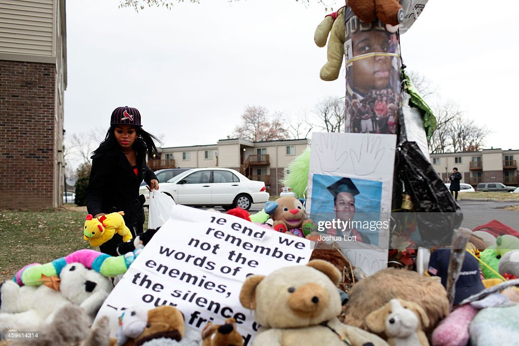 Marneisha Jones places a stuff animal at a makeshift memorial for Michael Brown November 22 2014 in Ferguson Missouri Brown a 18yearold black male...