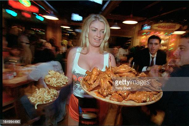 Marnie serves a burger 2 shots 3/4length and at table Jules brings a large platter of wings Sara and Marnie serve beer to guys with Hooters stickers...
