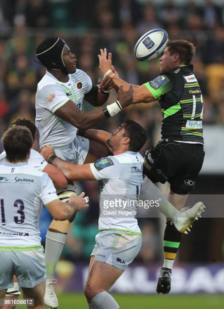Maro Itoje of Saracens challenges Piers Francis to the high ball during the European Rugby Champions Cup match between Northampton Saints and...