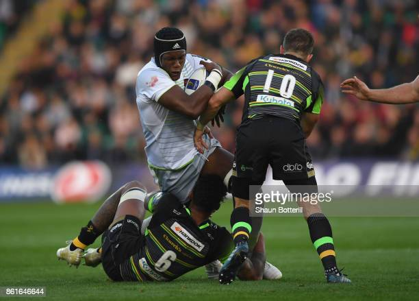 Maro Itoje of Saracens is tackled by Stephen Myler and Courtney Lawes of Northampton Saints during the European Rugby Champions Cup match between...