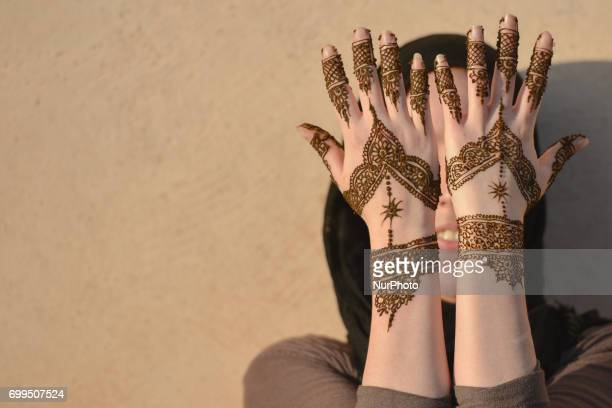 A Maroccan girl has decorative henna designs applied to her hands at a roadside stall ahead of Laylat alQadr celebrations in Rabat Morocco on 21 June...