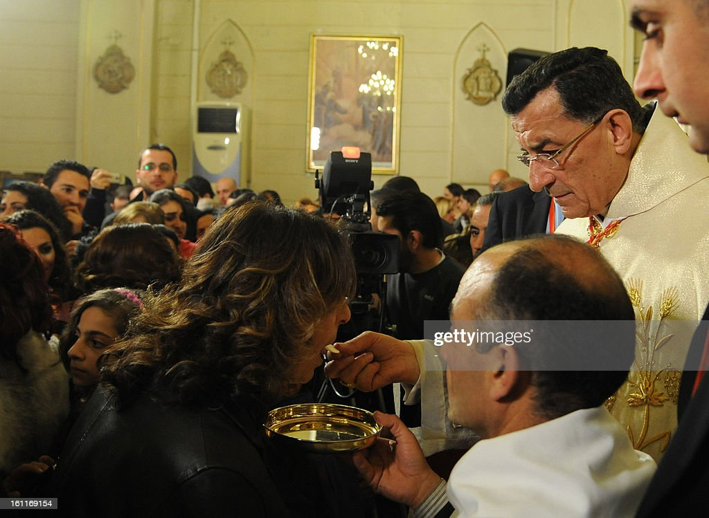 Maronite Patriarch Beshara Rai (R) gives holy communion to a worshiper at the Maronite Cathedral of Saint Anthony (Mar Antonios) in Bab Tuma, a predominantly Christian quarter of Damascus, on February 9, 2013. Rai's visit -- the first by a Maronite patriarch since Syrian and Lebanese independence in 1943 -- comes as the revolt against Syrian President Bashar al-Assad's regime nears the two-year mark. AFP PHOTO / STR