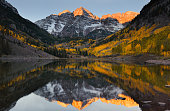 Beautiful sunrise touches Maroon bells peak at Maroon lake, Aspen, Colorado. Fall color of Aspen and reflection of Maroon Bells