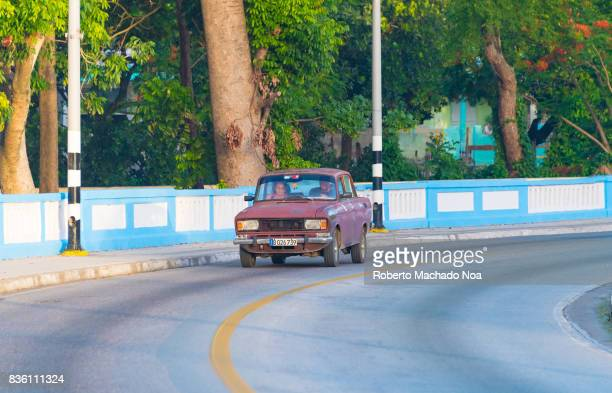 Maroon coloured Moskvitch old Russian car driving in the 'Central Road' traversing Santa Clara city