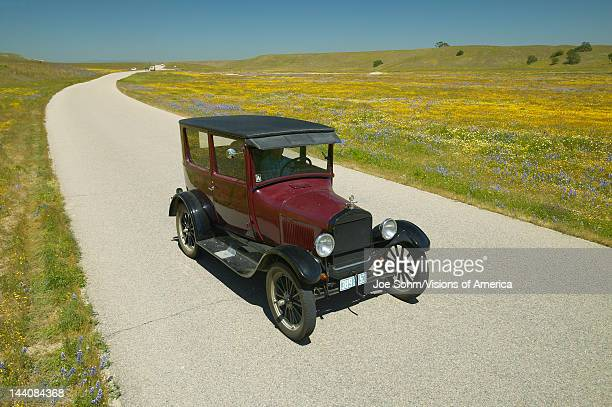 A maroon Model T driving down a scenic road surrounded by spring flowers off of Route 58 Shell Road CA
