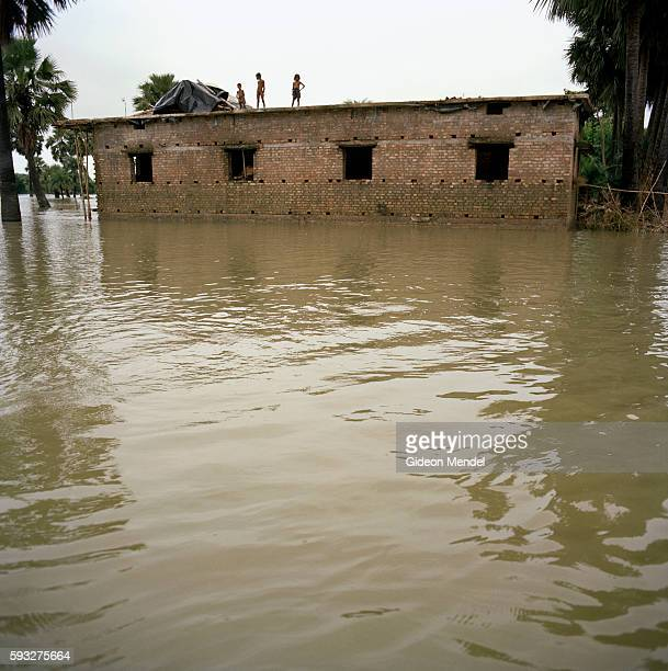 Marooned people live on the rooftops of sturdy brick houses which has been partly engulfed by rising floodwaters in Vardaha village in the east...