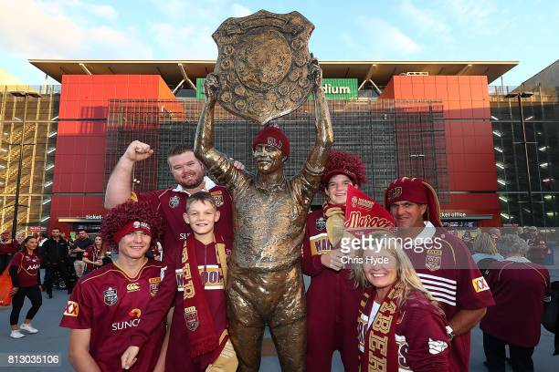 Maroons fans pose with the Wally Lewis statue before game three of the State Of Origin series between the Queensland Maroons and the New South Wales...