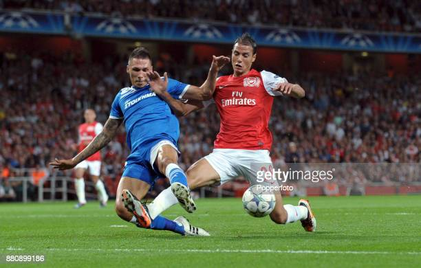 Marouane Chamakh of Arsenal and Jose Holebas of Olympiacos battle for the ball during a UEFA Champions League match at the Emirates Stadium on...