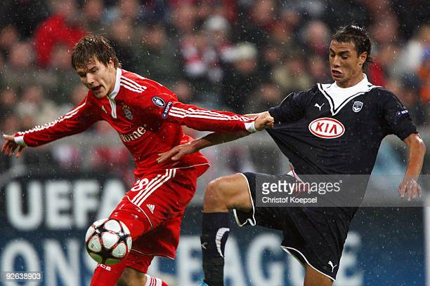 Marouane Chamakh of Bordeaux tackles Holger Badstuber of Bayern and scores his team's second goal during the UEFA Champions League Group A match...