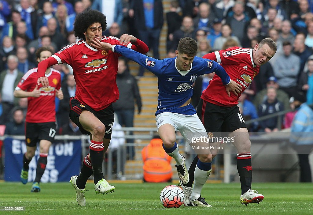 Marouane Fellaini and Wayne Rooney of Manchester United in action with John Stones of Everton during the Emirates FA Cup Semi Final match between Manchester United and Everton at Wembley Stadium on April 23, 2016 in London, England.
