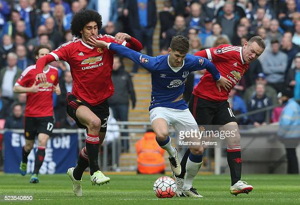 Marouane Fellaini and Wayne Rooney of Manchester United in action with John Stones of Everton during the Emirates FA Cup Semi Final match between...