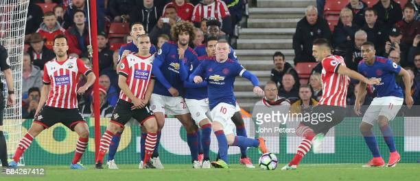 Marouane Fellaini Chris Smalling and Wayne Rooney of Manchester United defend a free kick from Dusan Tadic of Southampton during the Premier League...