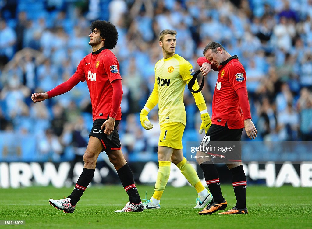 Marouane Fellaini, David De Gea and Wayne Rooney of Manchester United show their dissapointment after a heavy defeat during the Barclays Premier League match between Manchester City and Manchester United at the Etihad Stadium on September 22, 2013 in Manchester, England.