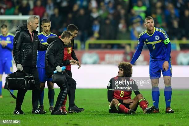 Marouane Fellaini midfielder of Belgium is comforted by Edin Dzeko forward of Bosnia Herzegovina after his injury during the World Cup Qualifier...