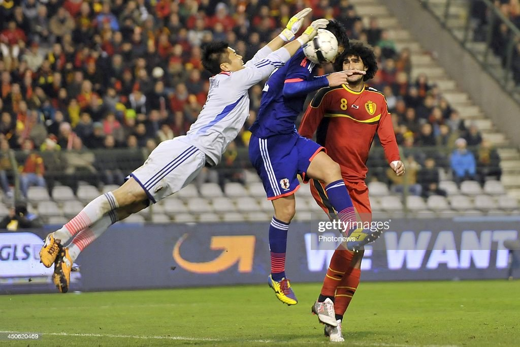 Marouane Fellaini of Belgium battles for the ball with Kawahima Eiji of Japan and Yoshida Maya of Japan during the international friendly match before the World Cup in Brasil between Belgium and Japan on November 19, 2013 in Brussels, Belgium