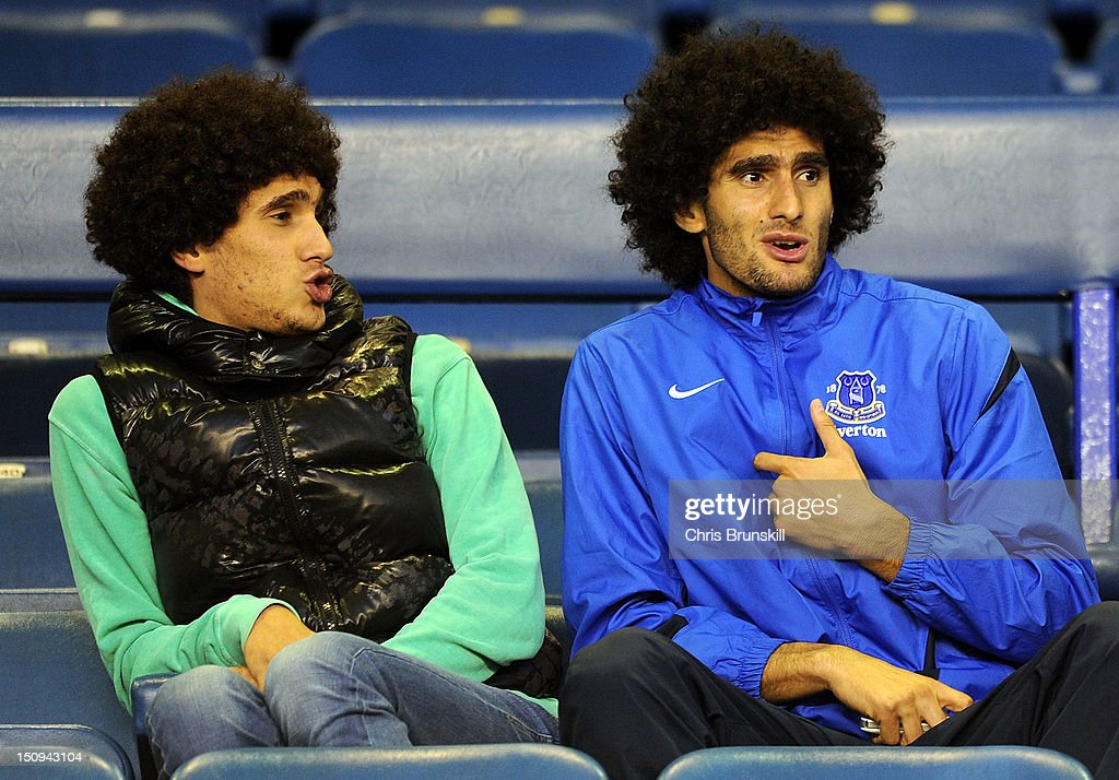 Marouane Fellaini of Everton looks on from the stand next to his brother during the Capital One Cup Second Round match between Everton and Leyton...