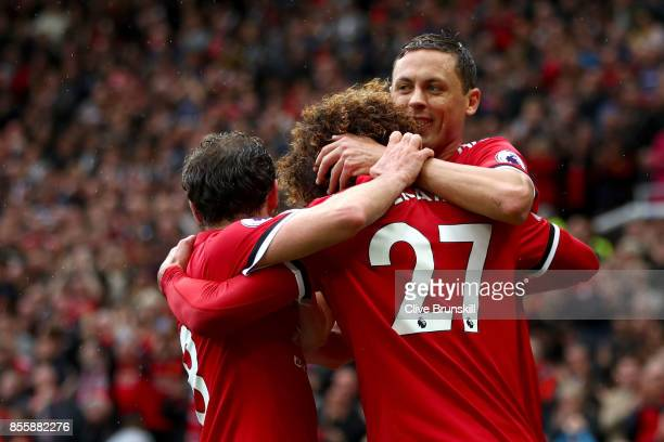Marouane Fellaini of Manchester United celebrates scoring his side's second goal with his team maets Juan Mata and Nemanja Matic during the Premier...