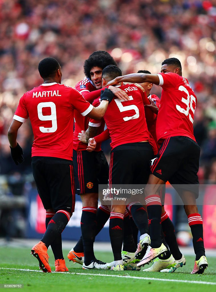 Marouane Fellaini of Manchester United celebrates with team mates after scoring the opening goal during The Emirates FA Cup semi final match between...