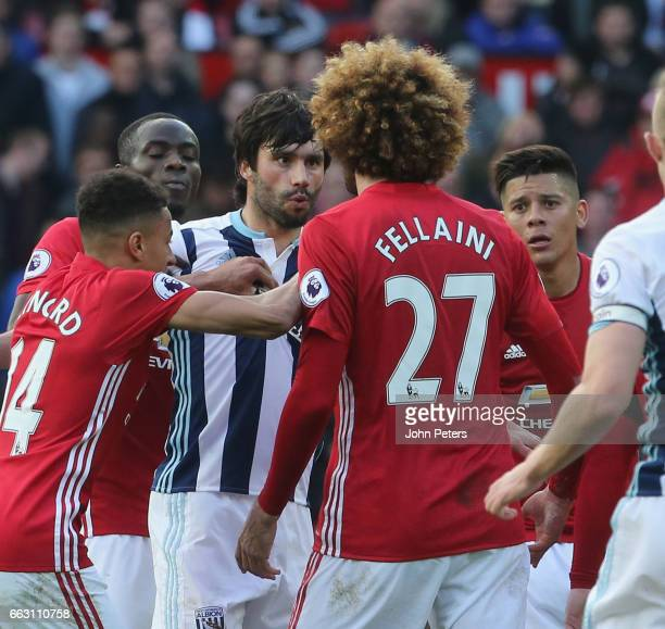 Marouane Fellaini of Manchester United clashes with Claudio Yacob of West Bromwich Albion during the Premier League match between Manchester United...