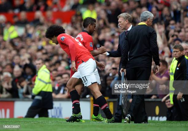 Marouane Fellaini of Manchester United comes on for team mate Anderson to make his debut watched by manager David Moyes during the Barclays Premier...