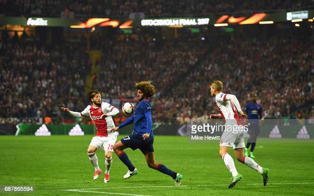 Marouane Fellaini of Manchester United controls the ball while under pressure from Lasse Schone of Ajax during the UEFA Europa League Final between...