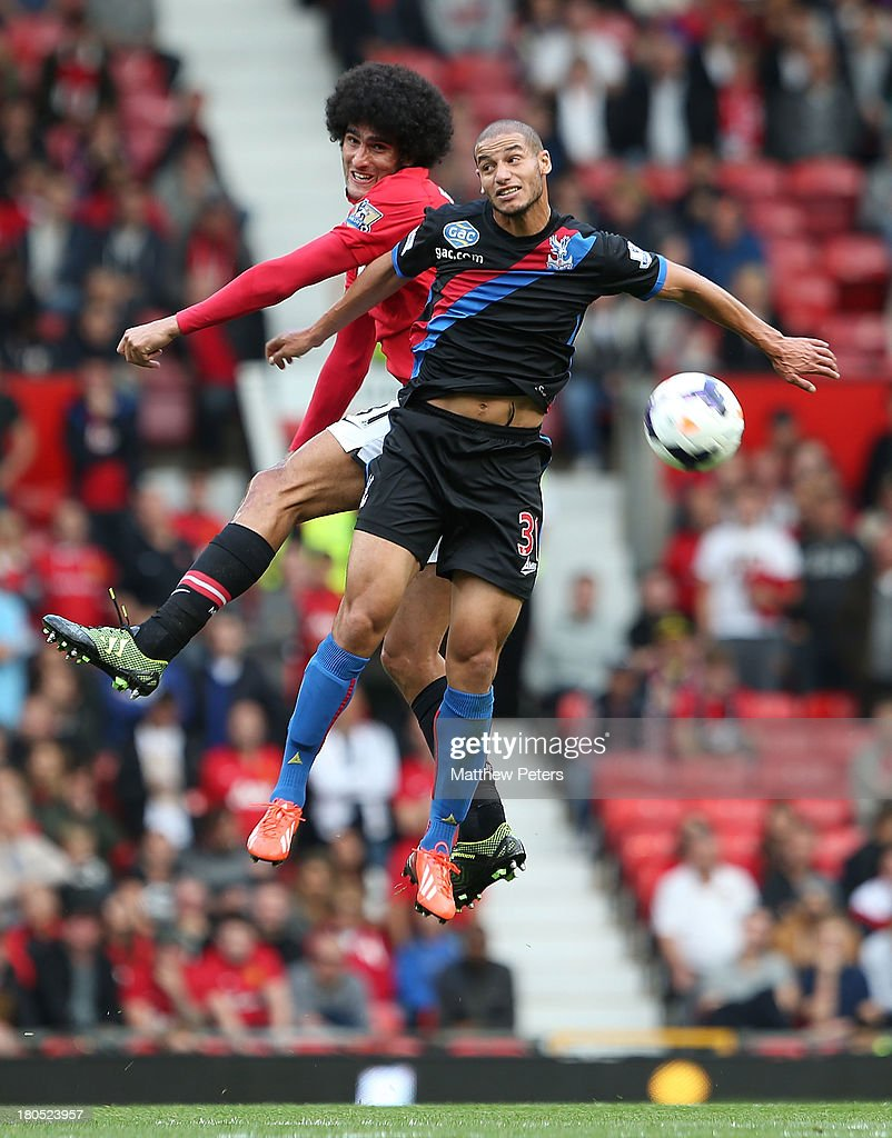 Marouane Fellaini of Manchester United in action with Adlene Guedioura of Crystal Palace during the Barclays Premier League match between Manchester United and Crystal Palace at Old Trafford on September 14, 2013 in Manchester, England.