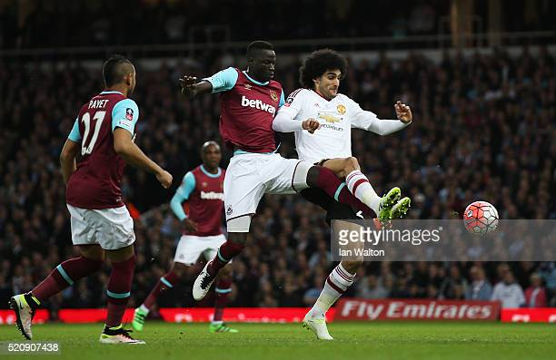 Marouane Fellaini of Manchester United is challenged by Cheikhou Kouyate of West Ham United during the Emirates FA Cup sixth round replay between...