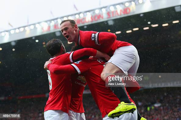 Marouane Fellaini of Manchester United is congratulated by captain Wayne Rooney and team mates as he scores their second goal with a header during...