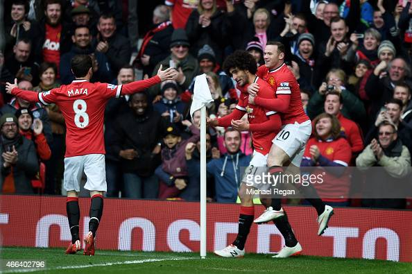 Marouane Fellaini of Manchester United is congratulated by teammates Juan Mata of Manchester United and Wayne Rooney of Manchester United after...
