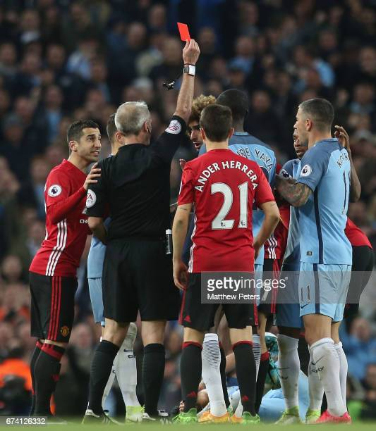Marouane Fellaini of Manchester United is sent off by Referee Martin Atkinson after clashRaheem Sterling with Sergio Aguero of Manchester City during...
