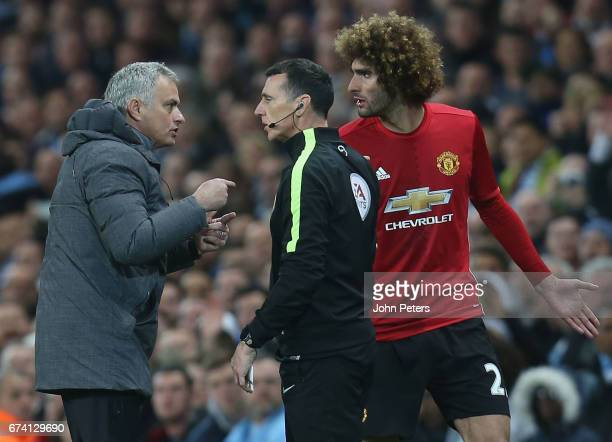 Marouane Fellaini of Manchester United pleads his innocence to Manager Jose Mourinho after clashing with Sergio Aguero of Manchester City during the...