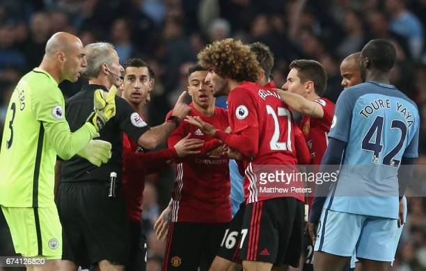 Marouane Fellaini of Manchester United pleads his innocence to Referee Martin Atkinson after clashing with Sergio Aguero of Manchester City during...