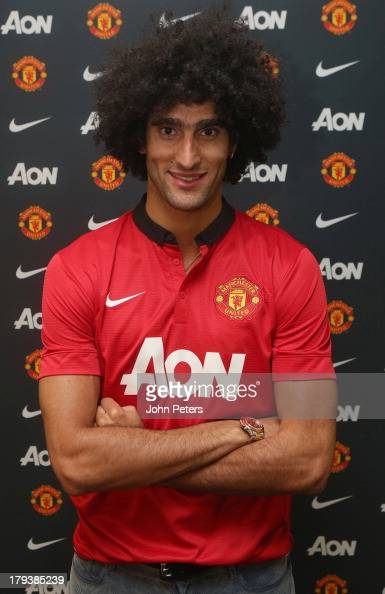 Marouane Fellaini of Manchester United poses in a Manchester United shirt after signing for the club at Aon Training Complex on September 2 2013 in...